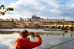 Toerist die Praag met Charles Bridge en Hradcany fotograferen Royalty-vrije Stock Afbeelding