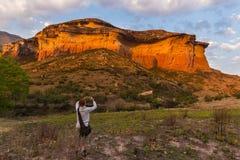 Toerist die slimme telefoon houden en foto nemen bij toneeldieklip door zonsonderganglicht wordt verlicht in de majestueuze Natio stock afbeelding
