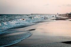 Toerist die van de Atlantische Oceaan genieten bij Oceaaneilandenstrand Noord-Carolina stock afbeelding