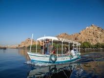 Toerist die van een rit op een kleine boot genieten die de rivier Nijl kruisen dichtbij Aswan, Egypte stock foto's