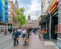 Toerist die vanaf het Damvierkant lopen naar het rood lichtdistrict op Damstraat stock afbeelding