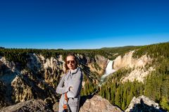 Toerist die waterval in Yellowstone overzien Stock Afbeelding