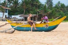 Toerist en lokale mensenzitting op een traditionele vissersboot van Sri Lankan bij strand Royalty-vrije Stock Foto's