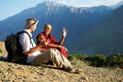 Toerist en monnik in bergen stock foto's