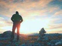 Toerist in groen jasje bij kiezelstenenpiramide op scherp de meningspunt van Alpen Het nationale park van Alpen Stock Afbeeldingen