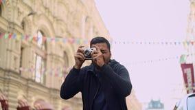 Toerist met camera die een schot van de historische bouw nemen stock footage