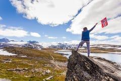 Toerist met camera en vlag in de bergen van Noorwegen royalty-vrije stock afbeelding