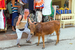 Toerist met een koe voor een kledingswinkel in Laxman Jhula India stock fotografie