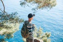 Toerist met een rugzak dichtbij het overzees royalty-vrije stock afbeelding