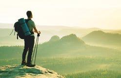 Toerist met in hand polen De zonnige rotsachtige top van het de lentelandschap royalty-vrije stock fotografie