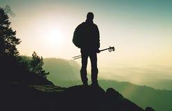 Toerist met in hand polen De zonnige rotsachtige top van het de lentelandschap stock afbeeldingen