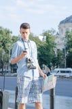 Toerist met kaart en mobiele telefoon Stock Fotografie