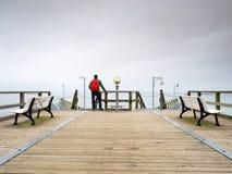 Toerist met rode rugzak op houten overzeese pijler Mens in trekkingskostuum Stock Foto's