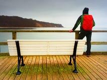 Toerist met rode rugzak op houten overzeese pijler Mens in trekkingskostuum Royalty-vrije Stock Foto