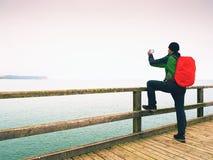 Toerist met rode rugzak op houten overzeese pijler Mens in trekkingskostuum Stock Afbeelding