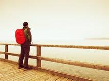 Toerist met rode rugzak op houten overzeese pijler Mens in trekkingskostuum Stock Foto