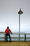 Toerist met rode rugzak op houten overzeese pijler Mens in trekkingskostuum Royalty-vrije Stock Afbeeldingen