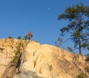 Toerist met rugzak die zich bovenop een heuvel bevinden en van de zonsondergang overzeese mening genieten Stock Afbeeldingen