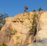 Toerist met rugzak die zich bovenop een heuvel bevinden en van de zonsondergang overzeese mening genieten Royalty-vrije Stock Foto's