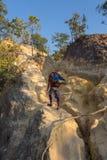 Toerist met rugzak die zich bovenop een heuvel bevinden en van de zonsondergang overzeese mening genieten Royalty-vrije Stock Fotografie