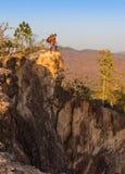 Toerist met rugzak die zich bovenop een heuvel bevinden en van de zonsondergang overzeese mening genieten Stock Afbeelding