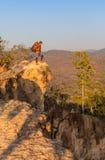 Toerist met rugzak die zich bovenop een heuvel bevinden en van de zonsondergang overzeese mening genieten Stock Foto
