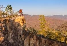 Toerist met rugzak die zich bovenop een heuvel bevinden en van de zonsondergang overzeese mening genieten Royalty-vrije Stock Afbeelding