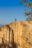 Toerist met rugzak die zich bovenop een heuvel bevinden en van de zonsondergang overzeese mening genieten Royalty-vrije Stock Afbeeldingen