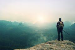 Toerist met rugzak en polen op klip en het letten op in diepe nevelige valleiblaasbalg Zonnige de lentedag in bergen Royalty-vrije Stock Afbeelding