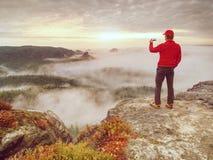 Toerist op de berg die foto's met de telefoon van het aanrakingsscherm nemen royalty-vrije stock foto's