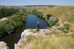 Toerist op een klip boven de rivier Stock Foto's