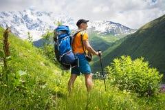 Toerist op een stijging in de bergen op een heldere zonnige dag Een jonge kerel met een rugzak op een bergachtig gebied op een wa Stock Afbeelding