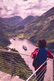 Toerist over Geirangerfjord met Noorse vlag stock afbeeldingen