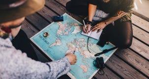 Toerist Planningsvakantie die wereldkaart gebruiken Stock Foto