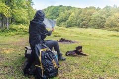 Toerist, zwarte rugzak, kaart en hond royalty-vrije stock afbeelding