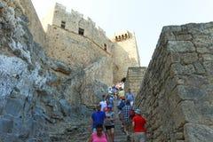 Toeristen bij de bovenkant van oude de Akropolisruïnes van Lindos Stock Foto