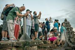 Toeristen bij de bovenkant van de tempel van Phnom Bakheng het fotograferen Royalty-vrije Stock Fotografie