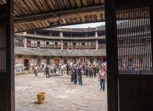 Toeristen binnen Tulou bij Huaan-de plaats van de de Werelderfenis van Unesco stock foto's