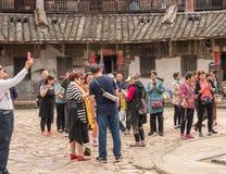 Toeristen binnen Tulou bij Huaan-de plaats van de de Werelderfenis van Unesco royalty-vrije stock foto