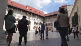 Toeristen in binnenbinnenplaats van het Koninklijke Kasteel van Wawel in Krakau stock video