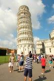 Toeristen die beelden van de Leunende Toren van Pisa nemen Royalty-vrije Stock Foto's