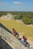 Toeristen die de Mayan Piramide van Kukulkan (ook beklimmen die als El Castillo wordt bekend) en ruïnes in Chichen Itza, het Schi Royalty-vrije Stock Afbeelding