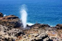 Toeristen die de Nakalele-gietgal op de kustlijn van Maui bewonderen Een straal van water en lucht wordt hevig binnen gedwongen u stock afbeeldingen
