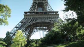 Toeristen die door de toren van Eiffel in Parijs, Frankrijk overgaan stock videobeelden