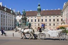 Toeristen die door paarden getrokken vervoer berijden Hofburg Wenen, Oostenrijk Royalty-vrije Stock Fotografie