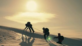 Toeristen die een klip van de bergsneeuw beklimmen Het uitrekken van een helpende hand de mensen helpen elkaar Groepswerk, groeps stock video