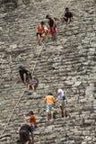 Toeristen die een Mayan piramide in Mexico beklimmen Stock Foto