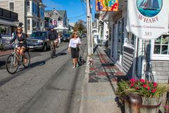 Toeristen die en onderaan hoofdstraat het onderzoeken lopen die de bicycling winkelt met auto's langs de straat en de leuke honde stock fotografie