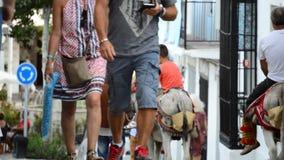 Toeristen die en op mensen lopen de letten zetten op een ezel in een typische straat van Mijas dorp in Andalusia op stock video