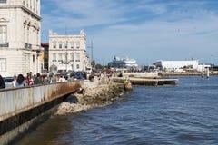 Toeristen die en van een zonnige dag in de banken van de Tagus-Rivier langs Ribeira das Naus Weg in de stad van Lissabon lopen ge Royalty-vrije Stock Foto